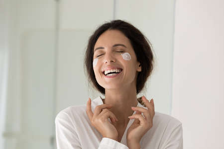 Close up of happy young Caucasian woman do daily morning beauty procedures or treatment in home bath. Smiling lady apply nourishing moisturizing face cream for healthy glowing skin. Skincare concept. Zdjęcie Seryjne