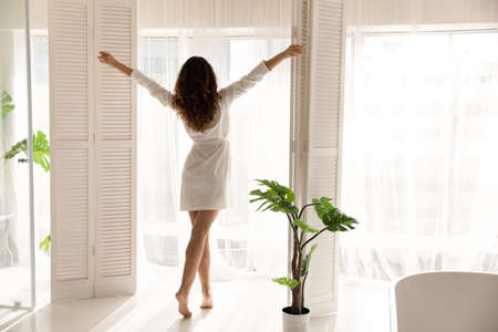 Back view of happy young woman in bathrobe open curtains look in window in cozy living room meet new sunny day. Overjoyed millennial female stretch relax enjoy good morning in own home or apartment. Zdjęcie Seryjne