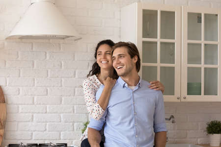 Smiling young Caucasian man and woman hug relax in cozy home kitchen look in distance dreaming thinking. Happy millennial couple renters enjoy good morning imagine visualize family future together.