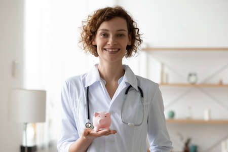 Portrait of happy young female general practitioner in medical uniform holding piggy bank in hands, advertising medical donations or charity help in clinic office, healthcare service payments concept.