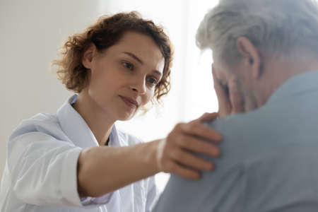 Head shot close up compassionate young general practitioner doctor supporting desperate stressed older mature retired man at appointment. Medical kindness, psychological help, soothing concept.