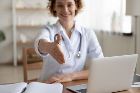 Smiling pleasant friendly young female general practitioner doctor reaching out hand for handshaking welcoming gesture, getting acquainted with new patient at checkup meeting or making deal in clinic.