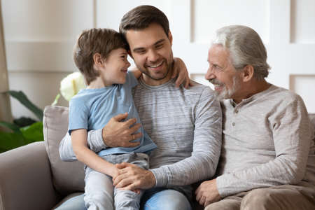 Happy three generations of men sit relax on couch in living room, have fun play together on family weekend. Smiling young man hug embrace cute little son, enjoy time with elderly father.