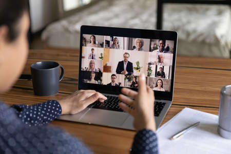 Back close up view of female worker talk speak on video call with diverse businesspeople from home office. Woman have webcam digital virtual conversation or online meeting on laptop with colleagues.