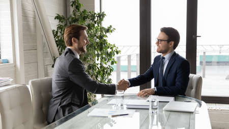 Wide panoramic view of successful young businessmen shake hands closing deal or making agreement at meeting in office. Smiling male colleagues partners handshake get acquainted at business briefing.