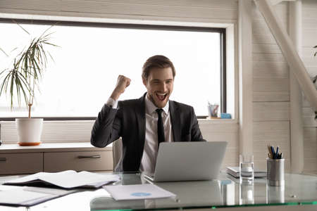 Excited young male CEO sit at desk in office look at laptop screen celebrate business win or success. Overjoyed Caucasian businessman feel euphoric triumph reading good news on computer at workplace. Stock fotó