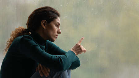 Unhappy millennial 20s Caucasian woman sit near window at home feel lonely depressed lack communication. Upset young female outcast lost in thoughts, distressed with loneliness or solitude indoors.