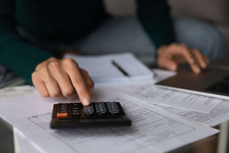 Crop close up of woman busy taking care of family financial paperwork, calculate expenses expenditures on calculator. Female manage household budget, pay online and do account. Saving concept.
