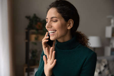 Smiling young Caucasian woman look in window waving greeting talking on smartphone on online call. Happy millennial female have pleasant cellphone conversation using mobile provider connection.