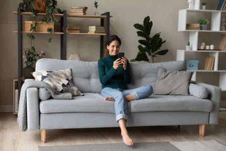Smiling young Caucasian woman sit relax on couch in living room talk on video call. Happy millennial female rest on sofa at home have webcam digital virtual communication on cellphone.