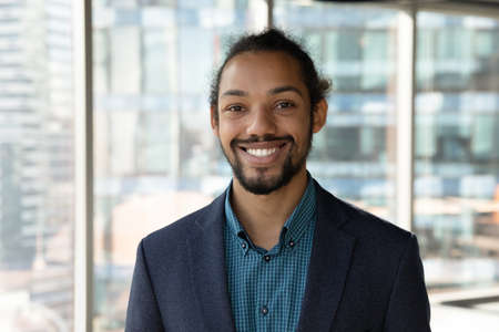 Headshot portrait of smiling young African American businessman in suit pose in own modern office. Profile picture of happy successful male boss or CEO in formalwear show confidence and leadership.