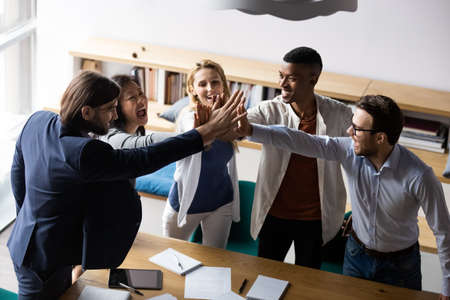 Above top view laughing emotional mixed race diverse teammates joining hands, giving high five to each other, celebrating shared corporate success or showing strong team spirit at office meeting.