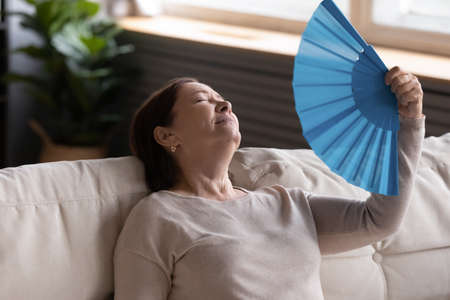 Close up exhausted middle aged woman waving blue paper fan, leaning back on couch at home, suffering from heat, high temperature or fever, sweaty mature female cooling in hot summer weather