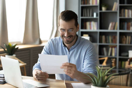 Smiling young businessman in eyeglasses looking at paper correspondence, reading pleasant good news. Excited happy male entrepreneur getting bank loan approvement notification at home office. Banco de Imagens
