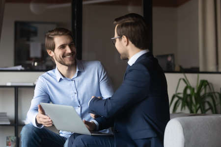 Happy colleagues shaking hands, greeting or making agreement, sitting in office with laptop, manager and client handshake, successful deal, hr manager recruiter congratulating candidate, getting job Banque d'images
