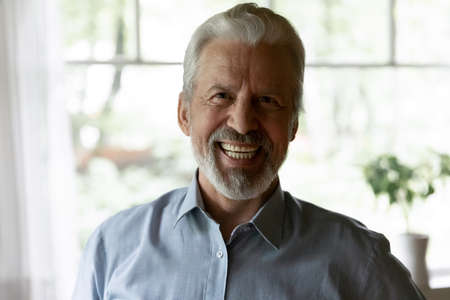 Close up laughing elderly grey haired man looking at camera, making video call to relatives or friends, using webcam, posing for profile picture, smiling happy mature male blogger shooting vlog Foto de archivo