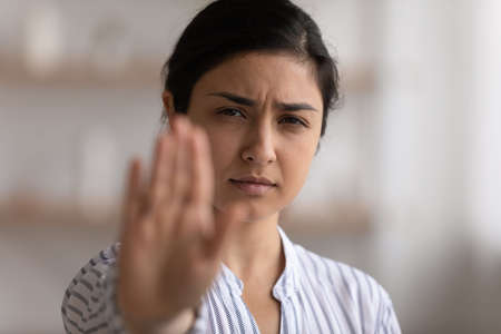 I say enough. Portrait of desperate indian woman showing stop gesture to any manifestations of racial gender discrimination. Strong hindu lady look at camera defend female right for free determination