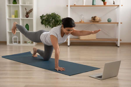 Active young female of indian ethnicity enjoy yoga at home practice static tiger asana. Mixed race woman trainee having personal fitness class online look at laptop screen imitate instructor movements Stock Photo