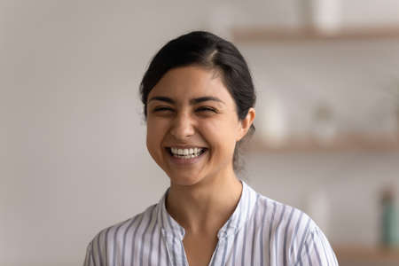 Sincere laughter. Head shot of excited young indian female having fun at home laughing on good witty joke. Joyful millennial mixed race woman demonstrating healthy white even teeth in beautiful smile