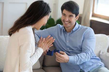 Close up smiling loving young man presenting box with wedding ring to excited woman, sitting on cozy couch together, excited boyfriend proposing marriage to girlfriend, engagement concept