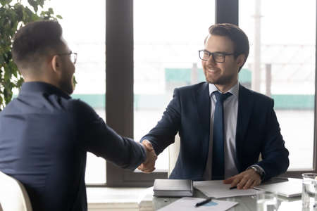 Smiling hr manager shaking hand of successful candidate after interview, Arabian man getting job, diverse business partners handshake, making great deal, agreement, employer greeting new employee