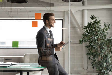 Smiling confident businessman holding tablet, looking in distance, standing in modern office behind glass wall, happy executive manager leader planning or visualizing future success, dreaming Foto de archivo