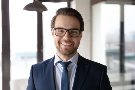 Head shot portrait smiling confident businessman wearing glasses and suit standing in modern office, executive manager company owner employee looking at camera, mentor coach posing for photo