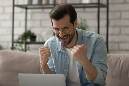 Close up overjoyed man wearing glasses looking at computer screen, showing yes gesture, reading unexpected news in message, excited businessman using laptop celebrating success, achievement