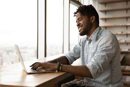 Smiling confident black african male correspond with client friend online typing texting email message on laptop keyboard. Happy young afro man skilled gamer enjoy playing pc video game in good mood