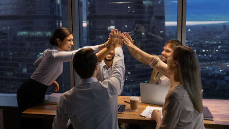 Motivated multinational team raise high fives on briefing after finding problem solution as successful brainstorm result. Happy workers unite hands above conference desk celebrate common achievement 版權商用圖片