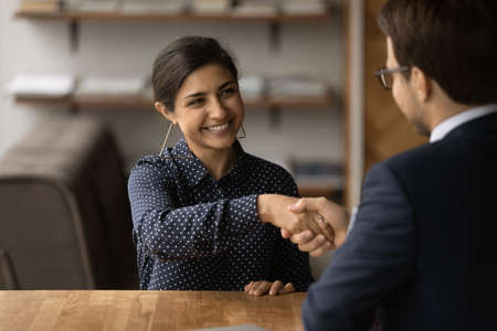 Greetings, you are hired. Happy young indian female successful job seeker shake hand of male hr manager being accepted on vacant place. Diverse business partners handshake close deal come to agreement Stock fotó