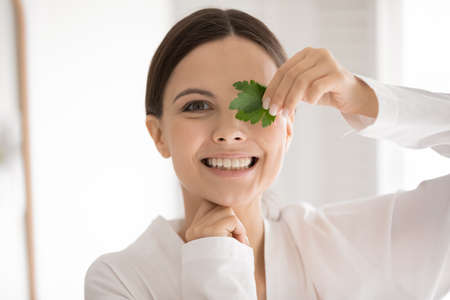 Close up portrait of smiling young Caucasian woman in bathrobe hold parsley recommend for healthy white teeth. Headshot of happy millennial female use greenery natural products for fresh breath.