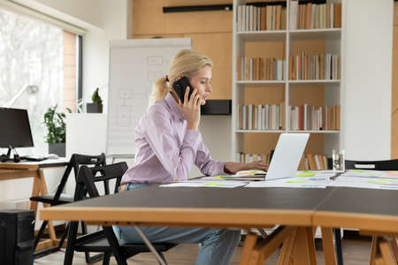 Busy office professional using laptop during phone call at workplace. Hardworking sales manager talking to client on cellphone, consulting internet, checking online data base. Communication concept