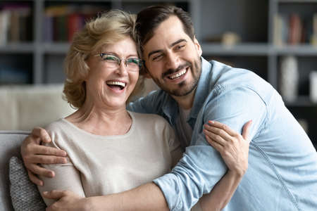 Happy middle aged retired woman relaxing on sofa with grown up handsome son, watching funny movie on tv, laughing at jokes at home. Affectionate young man cuddling older mother, having fun on weekend. Stockfoto