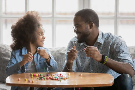 Close up smiling African American man and little daughter playing with colorful beads, talking, sitting on couch at home, crafting bracelets, family involved in creative activity, children education
