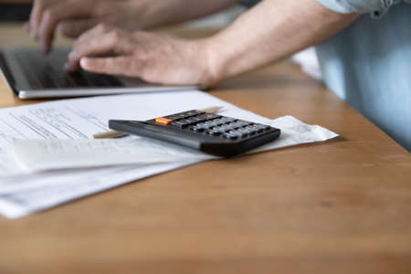 Close up of male client user of electronic bank system typing on laptop keyboard making payment online. Focus on calculator device lying on financial paper documents stack bills invoices notifications