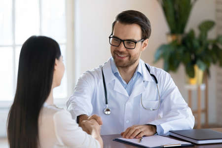 Happy millennial Caucasian male GP shake hand get acquainted greeting with female patient in hospital. Smiling young man doctor handshake close health insurance deal with woman client in clinic.
