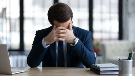 Upset distressed young Caucasian businessman sit at table in office think of business problem solution. Unhappy male boss or CEO stressed frustrated with company troubles. Failure concept.
