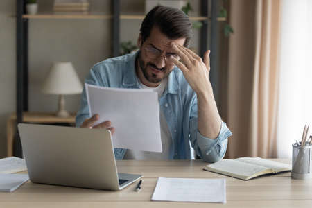 Confused shocked self employed businessman holding paper letter informing about accumulated bank debt unexpected financial problem. Upset stressed young male enterpreneur get loan application rejected Imagens