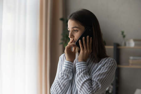 Sad millennial woman has difficult phone talk hold gadget by ear listen to unexpected bad news think on answer. Compassionate young lady support friend by cell try to help ponder on advice. Copy space
