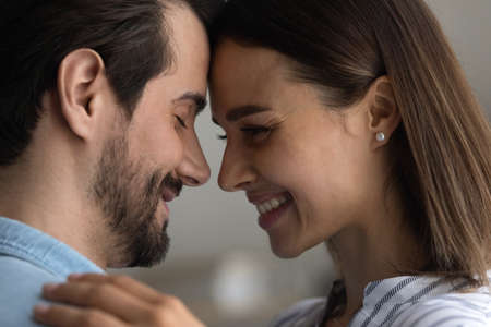 Warmth in relationship. Affectionate couple in love embrace close to one another touch foreheads enjoy intimate moment. Bonding lovers soulmates hug express tender feeling. Close up side view portrait