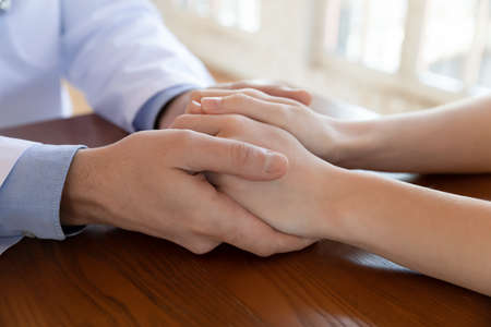Close up compassionate male gp doctor holding hands of stressed young female patient, giving psychological help, supporting soothing after getting bad health test results at checkup meeting.