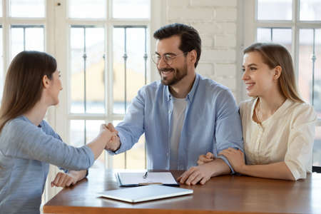 Happy young married family couple shaking hands with real estate agent, getting acquainted at meeting, celebrating making agreement or thanking for high quality professional service in office. Stockfoto