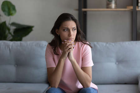Doubtful millennial arab female sitting on couch at home lost in serious thoughts. Thoughtful young woman of indian ethnicity looking aside pondering on making choice decision solving problem in mind