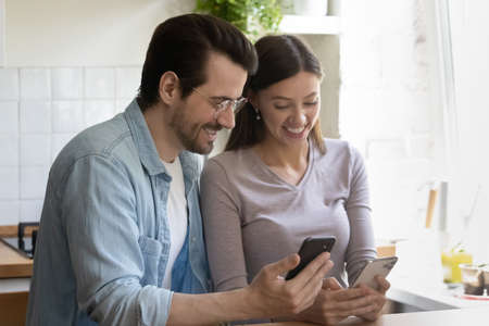 Overjoyed millennial couple sit at desk at home kitchen laughing using modern cellphones together. Happy young Caucasian man and woman have fun browsing surfing internet on smartphone gadgets.