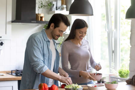 Happy millennial Caucasian couple cooking fresh salad in home kitchen in the morning together. Smiling young man and woman spouses have fun preparing healthy delicious diet food in own house.