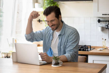 Excited millennial Caucasian man sit at table in kitchen look at laptop screen celebrate online lottery win. Overjoyed young male feel euphoric read good news or get promotion email on computer.