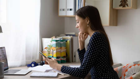 Wide banner panoramic view of millennial Caucasian female distracted from computer work use modern smartphone. Young woman sit at desk at home workplace look at cellphone scree, text or message. Stock Photo