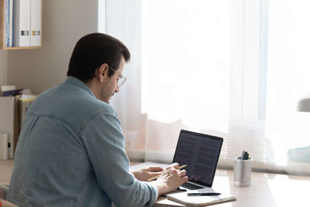 Back view of young man sit at desk at home office work distant on computer with paperwork documents. Millennial male look at laptop screen study or take course online, prepare report or research. Stock Photo
