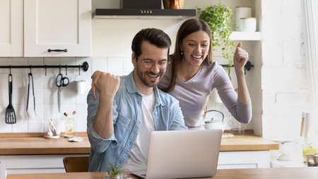 Wide banner panoramic view of overjoyed man and woman celebrate online lottery win on laptop. Excited young Caucasian couple feel euphoric triumph with good news or amazing sale deal on computer.